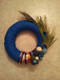 Wreath with blue ribbon,blue and gold satin decorative band ribbon,peacock feathers and nepal felt balls. I used 24cm yarn and hot glue to glue the blue ribbon over the yarn. Then I chose where I wanted to put the decorative ribbons and bands and hot glued them over the blue ribbon and complemented with the peacock feathers and nepal felt balls, to give a different touch.