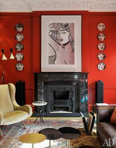 Orangy red walls with black accents in a bohemian room by the designer Antonella Skarsini.  I love the juxtaposition of the Fornasetti plates and the Lichtenstein? over the fireplace.