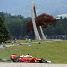 Sebastian Vettel driving past the iron Red Bull sculpture, at the Red Bull Ring.