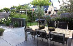 De onderhoudsvriendelijke tuin bij een nieuwbouwwoning aan het water heeft een natuurlijke maar moderne uitsraling. In het tuinontwerp is duidelijk rekening gehouden met de architectuur van de woning.