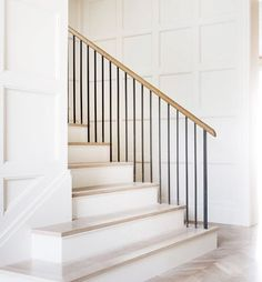 Simple light wood treads with white risers, square moulding detail and simple black spindles.