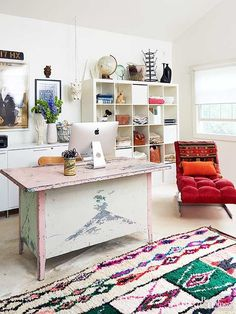 Mixing styles is a hallmark of Bohemian decorating. In this home office, a shaggy tribal rug combines with a salvaged desk, overstuffed chaise lounge, modern cube bookcase, and '70s accents. The white walls and floor allow the more vibrant pieces to pop in the space.