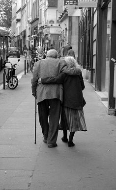 An elderly couple walking down the sidewalk in Paris. A lifetime of deep friendship and commitment!