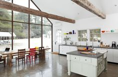 Floating Farmhouse - A pair of centuries-old hand hewn ceiling beams, salvaged from a Pennsylvania dairy barn, anchor the vaulted space. giveonehome