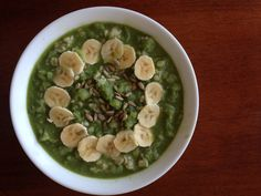 Green smoothie bowl for breakfast topped with sliced bananas and sprouted sunflower seeds.