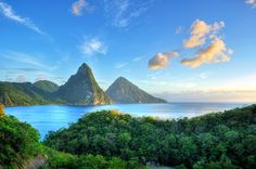The Pitons, St. Lucia's twin towering peaks and prime topographic feature, soar out of the sea to great heights. The Gros Piton (large piton...