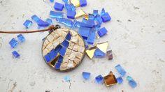 Bizantina. Mosaico da indossare. Bizantina è la linea di ciondoli in mosaico dedicati alla mia città, Ravenna. Smalti veneziani e vetri iridescenti si accostano alla naturalezza del marmo creando un vivo e raffinato contrasto. La luce penetra tra gli interstizi creando morbidi effetti di chiaroscuro tra una tessera e l'altra.   Disponibile in quattro colorazioni, specifica nell'ordine ROSSO, VERDE, BLU, NERO Diametro cm 3 Base color bronzo, cordino marrone chiaro o scuro.