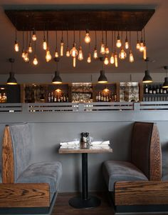 restaurante butacas retro bar madera gris sillas bancos bombillas suspendias estilo Edison
