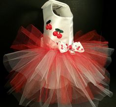 This crisp, springy tutu has a white satin bodice with cherry accents and is lined with cotton for comfort. There is a four layer