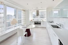White Modern Kitchen Design With White Laminate Countertop And White Sleek Cabinets Also White Gloss Round Breakfast Table And Stainless Range Hood: Ultra Modern Apartment Interior by Robert Couturier
