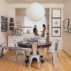 Splurge and Save Prioritize your spending. Instead of a more expensive chandelier, a paper lantern glows over the table in this dining room...