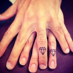 Tatuaje coincidente de dos diamantes situados en los dedos de una pareja. Artista tatuador: Ivy Saruzi