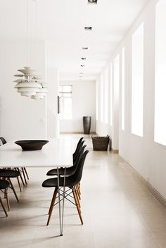 Eames dining chairs in black with light wood leg. So stunning in this minimal setting.