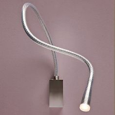 The Contardi Lighting FlexiLED Steel Wall Light optimizes flexible task and accent lighting with a serpentine body that bends and twists with ease. The sinuous body is topped with a warm LED light source which can be oriented for reading or accent light with a simple hand motion. Direct switching is provided on the wall plate that also features a rich metal finish. Composed of a steel mesh vertebrae covered with luxurious leather, the act of twisting the fixture not only creates different…