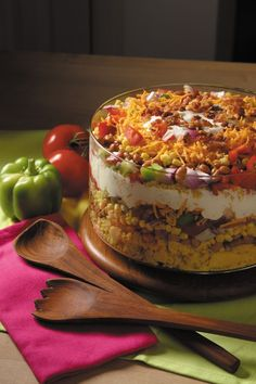 A layered salad, filled with corn, red and green pepper, and pinto beans, all topped with cheese and crumbled bacon