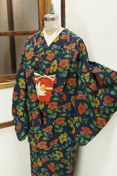紬のようなネップがアクセントになったネイビーの地に、染め出された椿のモチーフが愛らしいウールのアンサンブル(羽織と着物のセット)です。