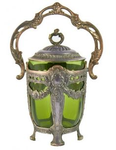 Opulent 19th Century Art Nouveau Metal and Green Glass Cookie Jar.  It has a silver plated copper core and is 29.5 cm high with raised handle.  Circa 1890 and English in origin.  The plating is worn and there is a chip on the glass.