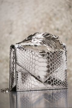ALINA CLUTCH Silver Python with Silver Feather feat. an Ornate Metallic Feather Handle, the Alina clutch radiates elegance and sophistication. Inspired by the same regal swan that roused the melodies of Tchaikovsky, the fluid jeté of Swan Lake's princess Purses 2017, Purses And Bags, My Bags, Georges Chakra, Ralph And Russo, Chanel, Fashion Weeks, Beautiful Bags, Evening Bags