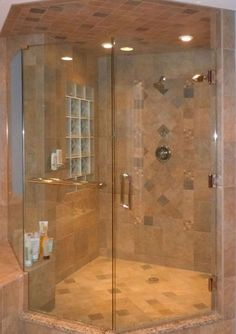 This modern shower features porcelain tiles in shades of natural slate with border and accent tiles in a raised relief design. A glass block window provides privacy and light.