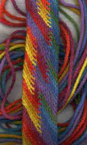 SCOT braid with Twined Linking. Cords 3/8 inches diameter of rug wool,  by starting at the top with long cords and working downwards. Experimental piece to see what would happen to the beginning orderly spectrum of colours if I worked the twined linkings at various strategic places. The colours appear and disappear in intriguing ways. Width 2 and 1/2 inches