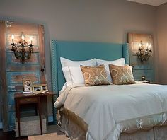 These salvaged old doors make a grand statement on either side of the bed, especially with the lighting attached to it.  That headboard is pretty beautiful as well.