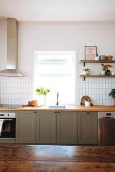 A Brisbane fixer-upper was revived by A Pair and A Spare - Olive green shaker cabinet doors pair beautifully with white tiles, a timber bench top and silver appliances. Wooden Kitchen Cabinets, Green Cabinets, Kitchen Backsplash, Pantry Cabinets, White Cabinets, Green Kitchen Cupboards, Coloured Kitchen Cabinets, Wooden Countertops, Kitchen Colors
