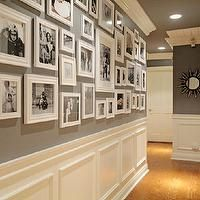 Fabulous hallway features black and white photo wall on dark gray walls (& ceiling) over white wainscoting