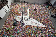Vik Muniz, Paper cranes for Japan,     2011    In July, Vik generously donated his time, vision and his Brooklyn studio team to create a large-scale piece of art from thousands of paper cranes sent from around the world along with wishes of hope and healing.     Photographs by  Andrew Moore for The New York Times