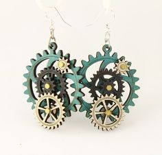 """Made in U.S.A Style # 5003E Size 1.65"""" x 1.5"""" Kinetic Gear Earring 5003E All Gears Move! Comes as shown -Aqua Marine/Natural Wood/Black Satin Made from sustainably sourced materials Laser-cut wood Stained with water based dye Ear wires are silver-finished 3041 stainless steel with new electrophoretic-coating that resists tarnishing"""