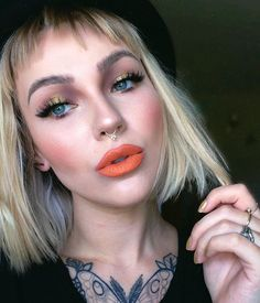 """DEAD over #katvondbeauty studded lipstick in """"solo""""  it is the coolest metallic golden orange  SO NECESSARY!  #anastasiabeverlyhills world traveler palette on the eyes, light to medium contour kit on the face, dip brow in taupe (fluffball eyebrow how-to video in the previous post)  #houseoflashes in featherette  #makeupgeek blush in """"summer fling""""  custom septum jewelry by @loandchlo"""
