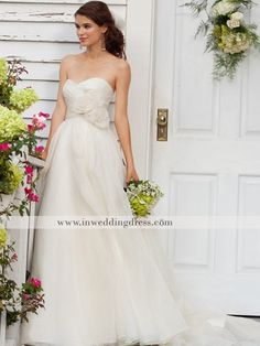 Gorgeous gown features in great Organza. Strapless top accents a graceful wraparound sweetheart neckline. Natural waistline is highlighted with flattering flowers on one side. Full and flared skirt drapes down to the floor in dramatic effect and extends out a sweep length train in the back. This dress is fully lined. Good option as a beach wedding dress.