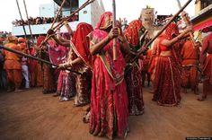 """Women from Barsana village, home of Krishna's lover, Radha, come to Krishna's village, Nandgaon, during the Lathmar Holi celebrations."