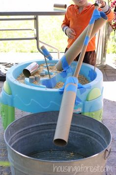 Using chicken feed. Transfer feed from one bin to another using tubes. Approved by Rosie Revere Engineer, book by Andrea Beaty. #STEM