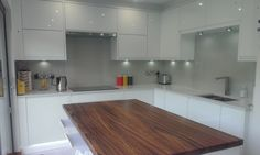 Modern white gloss kitchen with integrated handle doors, quartz worktops & zebrano worktops. Designed, supplied and installed by JDW Interiors Ltd