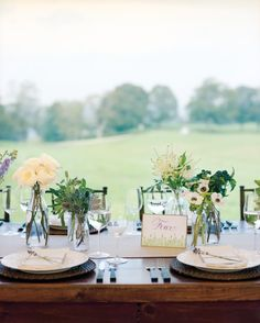 Vintage glass bottles, each filled with a single type of flower -- garden roses, dahlias, privet berries, delphinium, Queen Anne's lace, astilbe, or anemones -- lended a pastoral look to wooden tables in Reading, Vermont.
