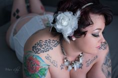 Curvy tattooed beauty with white hair flower and corset created by Lily Angiolini, a Central Michigan boudoir photographer of Miss Lily Photography  #tattoo #curvy #boudoir #misslilyphoto