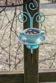 Bird feeder made out of a ceramic tea cup and saucer held in place with artfully crafted metal rods attached to a piece of wood