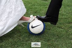 Bride and groom with their foot on a soccer ball.