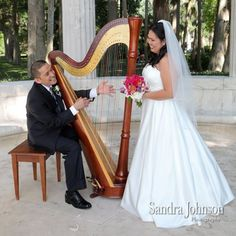 Fun pic by Sandra Johnson Photography of the bride and groom with the harp!
