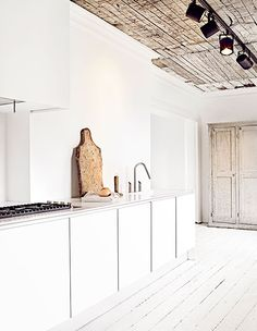 home of Marie Olsson Nylander -  great contrast between white kitchen and natural, raw elements