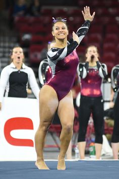 University of Denver gymnast Nikole Addison smiles while dancing through her floor choreography as teammates cheer her on in the background. Photo taken on March 7, 2015, in Magness Arena at DU.