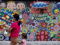 A mother holding a baby walks past graffiti painted on a wall in Manila