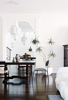 White walls, white chandeliers,  brown dining table, black chair, wood chair, white planter, and hardwood floors
