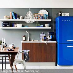 """Der konsequente Retro-Look dieser Wohnküche wird durch den blauen Kühlschrank von Smeg komplettiert. Echte Hingucker sind außerdem der Stuhl """"Tolix"""" in Weiß …"""