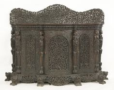 An Anglo-Indian hardwood credenza, mid-19th century, the shaped upstand with pierced and carved foliate decoration above a solid serpentine top, with central arched cupboard flanked to either side by further cupboards interspersed by figural columns, raised on a pierced and carved foliate-decorated apron on lion's mask paw feet Sold for £1650 on 14th March 2017