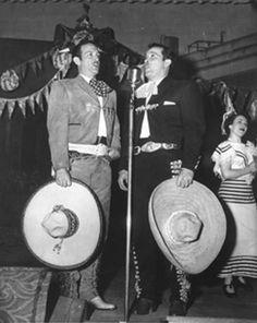 Pedro Infante Cruz cantando con Jorge Negrete en el escenario de un teatro.