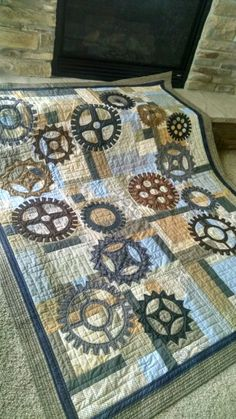 """Andrew's college graduation quilt. Background patches are """"turning twenty again"""" pattern and the needle turn appliqued gears are my designs."""