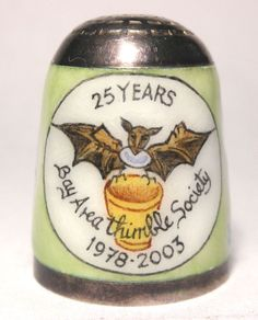 This mint sterling silver and enamel thimble was beautifully hand painted by the late Peter Swingler. It is fully marked inside the top including P S in diamond shaped lozenges. In 2003 several of the BATS (Bay Area Thimble Society) members commissioned a 25th club anniversary thimble from Mr. Swingler. This is a one of a kind thimble, designed by Martha, depicting the BATS logo and dates on the front with her name on the back. It's signed 'P.Swingler' to the bottom right of the…