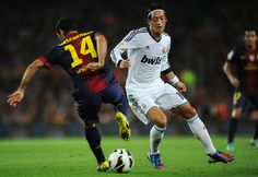 Javier Mascherano (L) of Barcelona shields Mesut Ozil of Real Madrid from the ball during the la Liga match between FC Barcelona and Real Madrid at the Camp Nou stadium on October 7, 2012 in Barcelona, Spain.