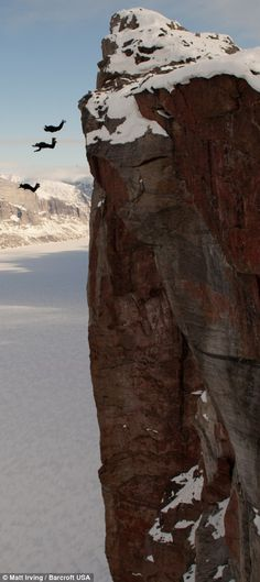 That's some triple jump! 3 daredevil basejumpers leaping off 2,000ft snow-capped…